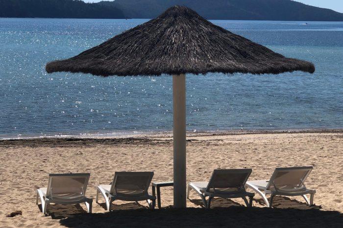 Loungers on beach under umbrella